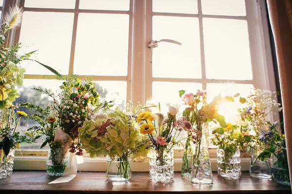 Wild Vintage Flowers Jars Vases Colourful Homemade Village Hall Wedding http://hollydeacondesign.com/