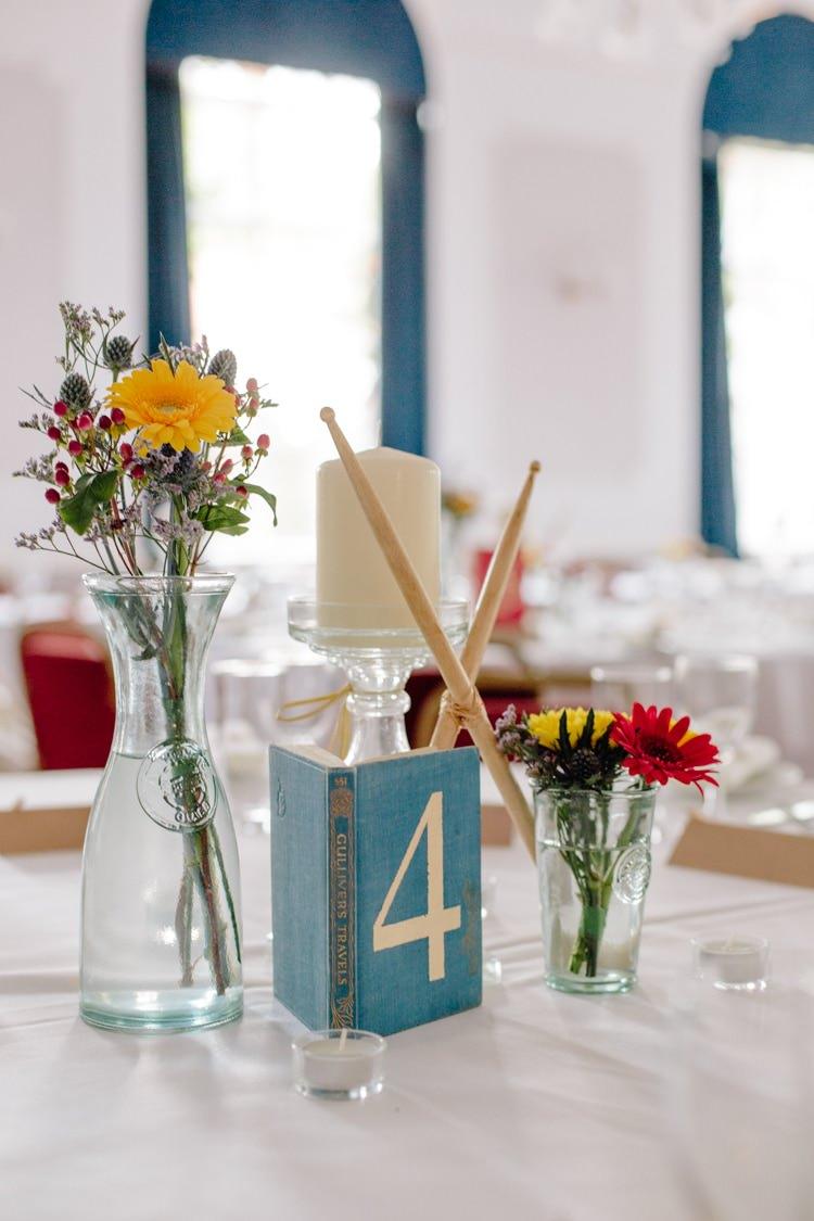 Drumsticks Books Centrepiece Flowers Table Decor Informal Vintage Personal Wedding http://www.marknewtonweddings.co.uk/