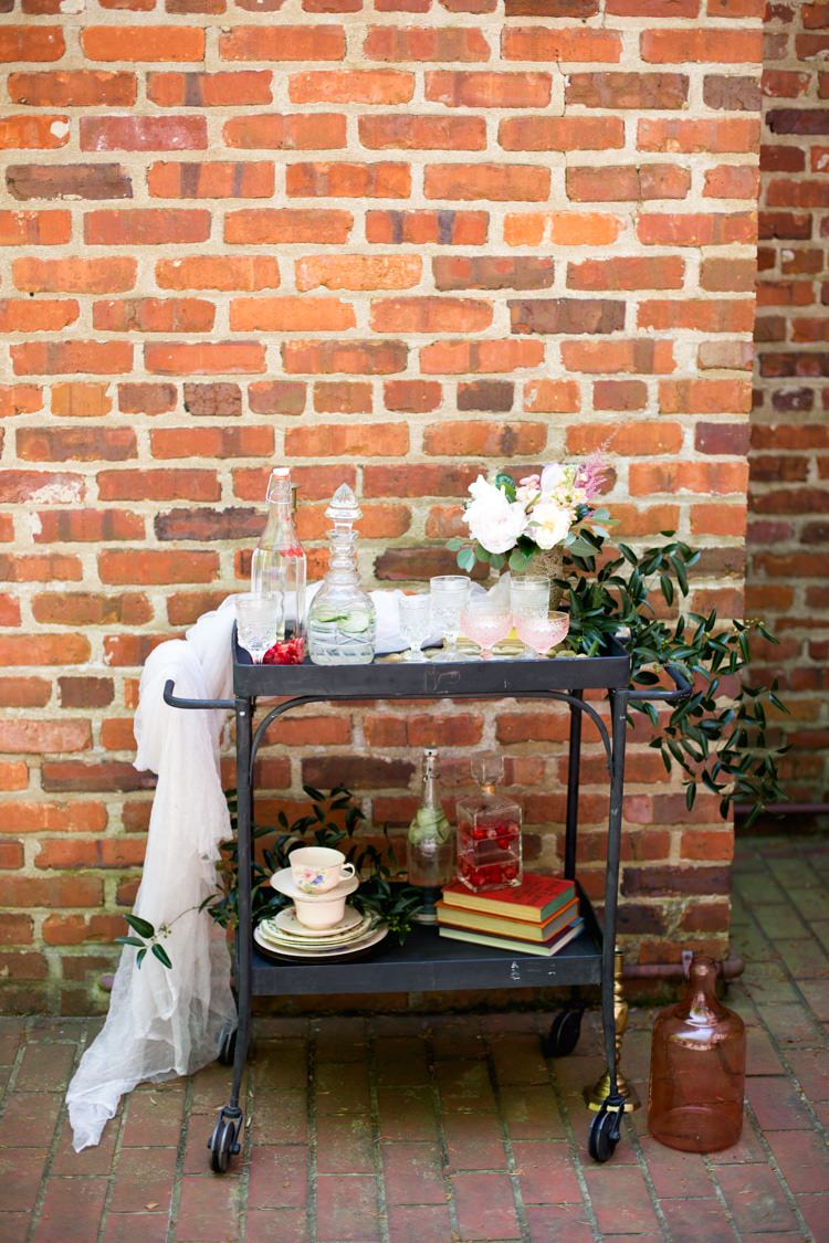 Drinks Tray Retro Décor Glass Bottles Blush Glasses Tea Cups Books Pink Green Florals Tulle Vase Brick Wall Romantic Vintage Wedding Ideas http://katymurrayphotography.com/