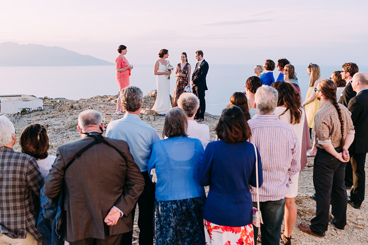 Outdoor Ceremony Bride Backless Bridal Gown Groom Navy Suit Blue Striped Tie Guests Ocean Breathtaking Intimate Mykonos Destination Wedding http://www.annapumerphotography.com/