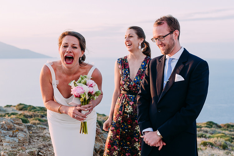 Outdoor Ceremony Bride Backless Bridal Gown Pink White Lillies Bouquet Groom Navy Suit Blue Striped Tie Celebrant Candid Breathtaking Intimate Mykonos Destination Wedding http://www.annapumerphotography.com/