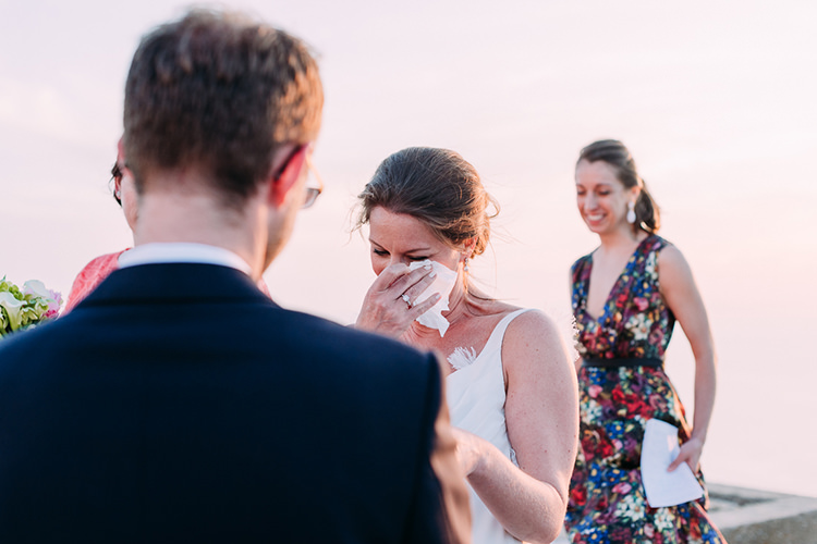 Outdoor Ceremony Bride Backless Bridal Gown Engagement Ring Happy Tears Celebrant Breathtaking Intimate Mykonos Destination Wedding http://www.annapumerphotography.com/