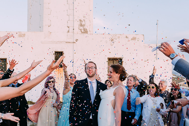 Outdoor Ceremony Bride Backless Bridal Gown Groom Navy Suit Blue Striped Tie Guests Confetti Celebrations Breathtaking Intimate Mykonos Destination Wedding http://www.annapumerphotography.com/
