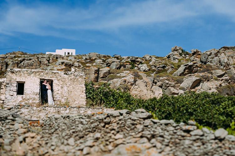 Bride Backless Bridal Gown Groom Hug Brick Stones Blue Sky Breathtaking Intimate Mykonos Destination Wedding http://www.annapumerphotography.com/