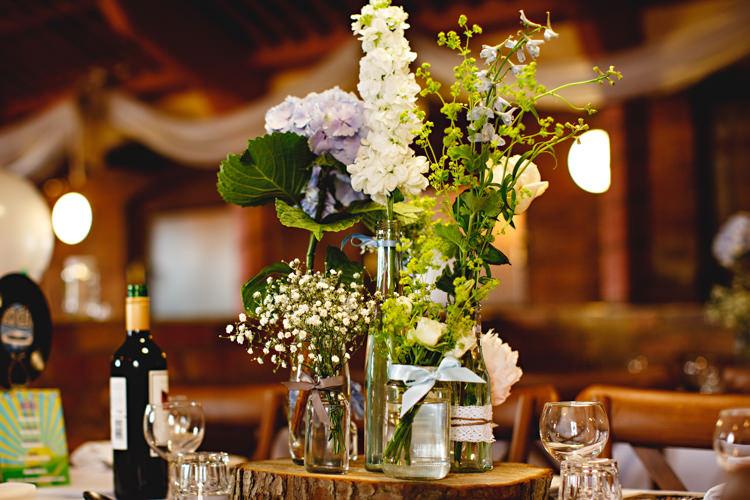Flowers Jars Log Decor Ribbons Blue Rustic Casual Festival Feel Barn Wedding http://hbaphotography.com/