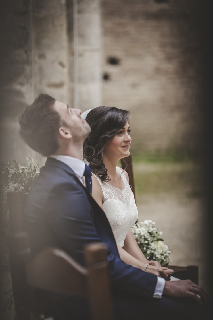 Outdoor Ceremony Bride Lace Sleeveless Bridal Gown Loose Curls Groom Navy Blue Suit Polka Dot Tie Gypsophila Wooden Chairs Atmospheric Abbey Tuscany Wedding http://www.angelicabraccini.com/
