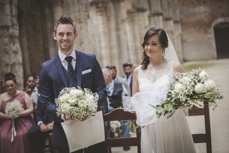 Outdoor Ceremony Bride Lace Sleeveless Bridal Gown Loose Curls Veil Groom Navy Blue Suit Polka Dot Tie White Pocket Square Bouquet Cream Roses Gypsophila Bridesmaid Guests Atmospheric Abbey Tuscany Wedding http://www.angelicabraccini.com/