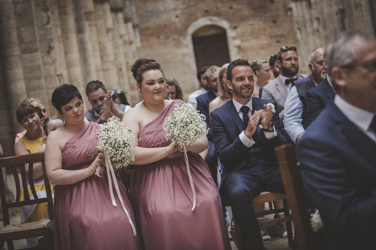 Outdoor Ceremony Bridesmaids Rose One Shoulder Dresses Bouquet Gypsophila White Ribbon Guests Wooden Chairs Atmospheric Abbey Tuscany Wedding http://www.angelicabraccini.com/
