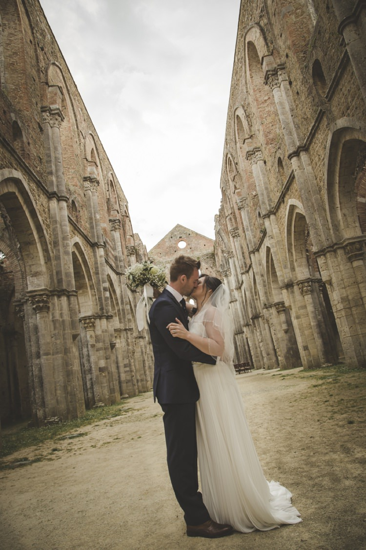 Outdoor Ceremony Bride Lace Sleeveless Bridal Gown Loose Curls Veil Bouquet Cream Roses Gypsophila Groom Navy Blue Suit Polka Dot Tie Kiss Atmospheric Abbey Tuscany Wedding http://www.angelicabraccini.com/