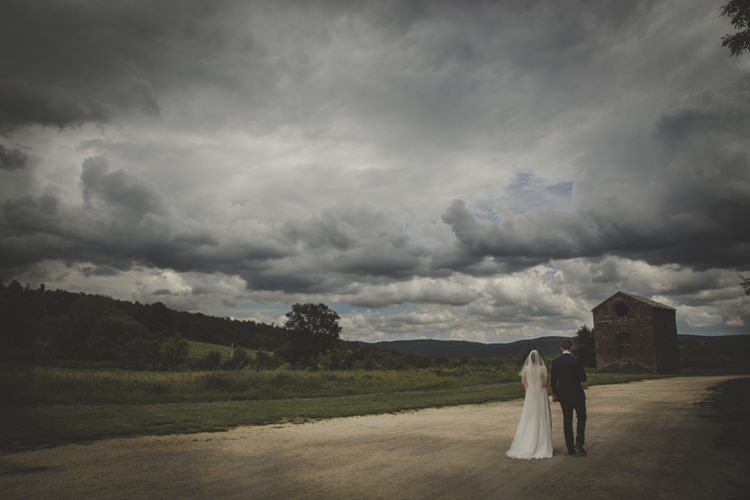 Bride Lace Sleeveless Bridal Gown Veil Groom Navy Blue Suit Dark Cloudy Skies Green Hillside Dirt Road Atmospheric Abbey Tuscany Wedding http://www.angelicabraccini.com/