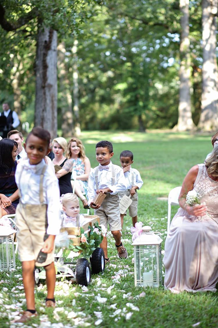 Page Boys Entrance White Shirts Beige Shorts Pale Pink Bow Ties Tan Leather Shoes Wooden Cart Candle Lanterns Trees Grass Flower Petals Guests Soft Romantic Woodland Wedding Tennessee http://www.jessicaleephotographicart.com/