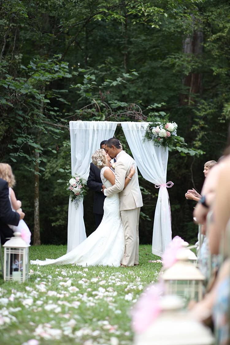 Outdoor Ceremony Bride Lace Mermaid Bridal Gown With Straps Floral Hairpiece Groom Beige Suit White Curtains Floral Bouquets Hydrangeas Roses Flower Petals Candle Lanterns Guests Trees Grass Soft Romantic Woodland Wedding Tennessee http://www.jessicaleephotographicart.com/