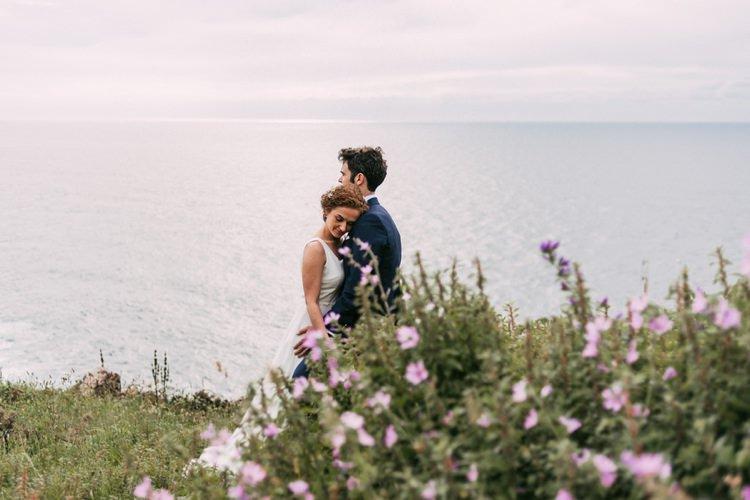 Bride Round Neck Crepe Tulle Bridal Gown Floral Hairpiece Groom Navy Blue Suit Purple Wildflowers Green Hills Ocean Romantic Bohemian Spain Wedding http://saralobla.com/