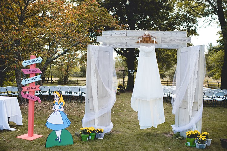 Outdoor Ceremony White Archway Curtains Strapless Bridal Gown Alice Cartoon Wooden Sign Potted Flowers Alice in Wonderland Wedding Pennsylvania http://www.julieflorophotography.com/