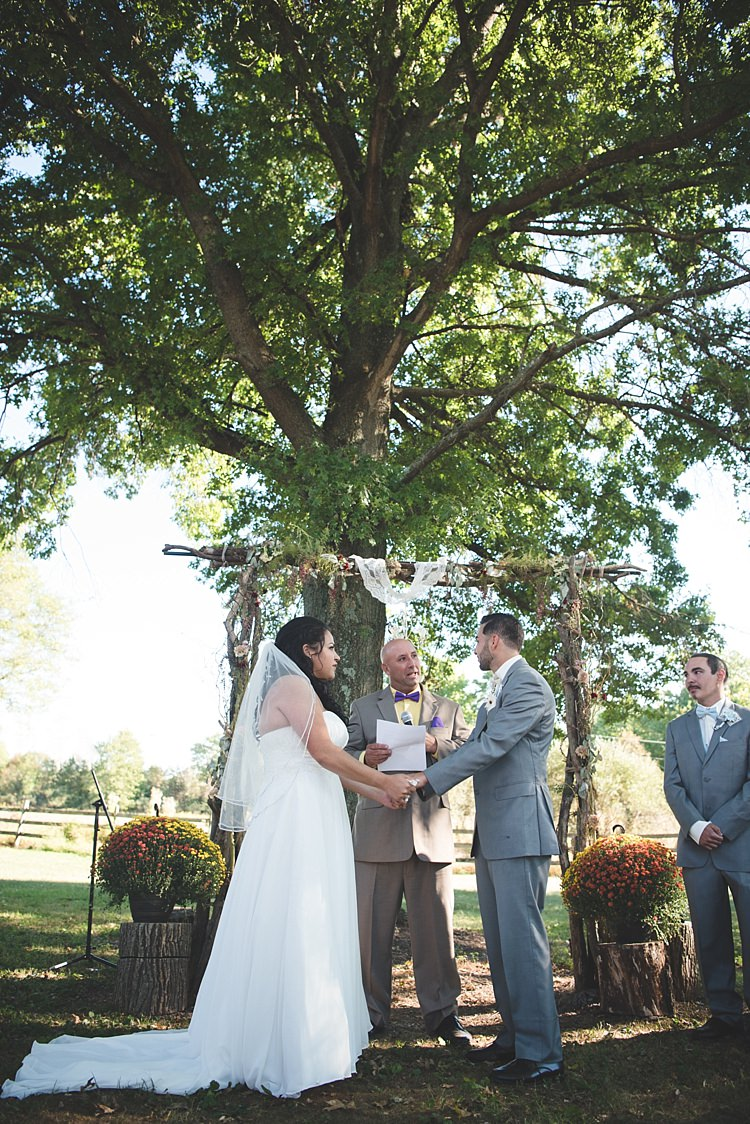 Outdoor Ceremony Decorated Arch Bride Strapless Gown With Train Veil Groom Grey Suit White Bowtie Celebrant Leafy Tree Potted Flowers Alice in Wonderland Wedding Pennsylvania http://www.julieflorophotography.com/