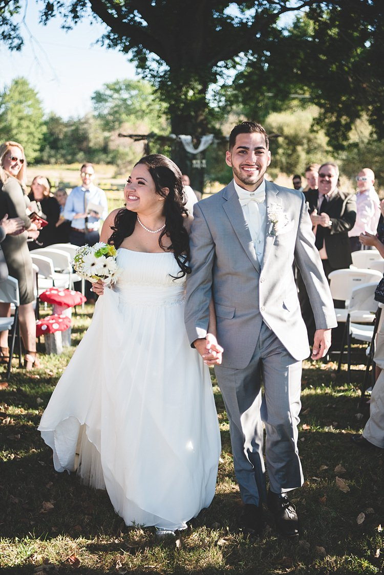 Outdoor Ceremony Decorated Arch Bride Strapless Gown With Train Veil Bouquet White Yellow Gerbera Groom Grey Suit White Bowtie Guests Smiles Alice in Wonderland Wedding Pennsylvania http://www.julieflorophotography.com/