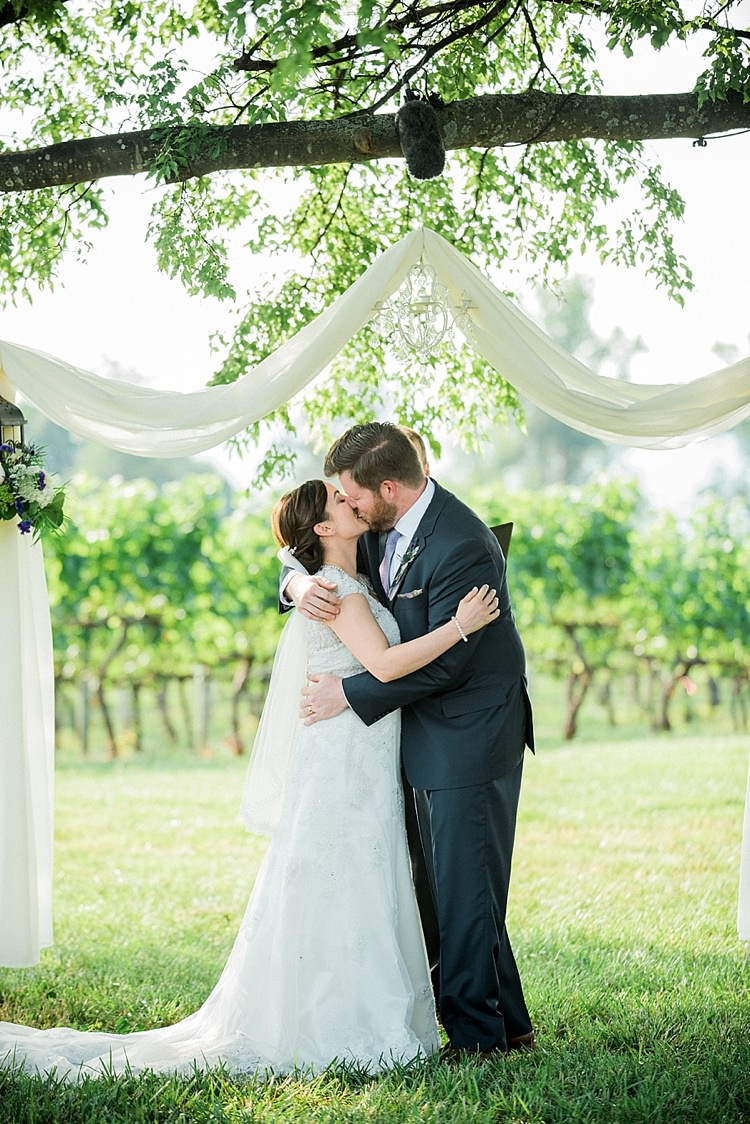 Outdoor Ceremony Bride Lace Cap Sleeve Bridal Gown Veil Groom Navy Suit Purple Tie Hanging Décor Chandelier White Fabric Kiss Outdoor Spring Vineyard Wedding Tennessee http://www.juicebeatsphotography.com/