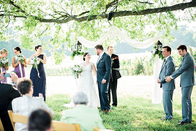 Outdoor Ceremony Bride Lace Cap Sleeve Bridal Gown Bouquet Groom Navy Suit Purple Tie Bridesmaids Groomsmen Hanging Décor Outdoor Spring Vineyard Wedding Tennessee http://www.juicebeatsphotography.com/