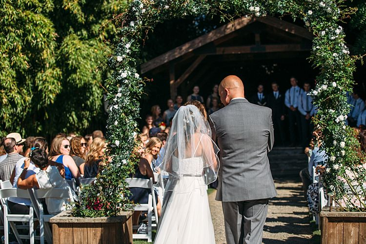 Outdoor Ceremony Entrance Bride Lace Tulle Bridal Gown Grey Sash Veil Father Guests Floral Arch Organic Farm Wedding Washington http://www.katiedayphotos.com/