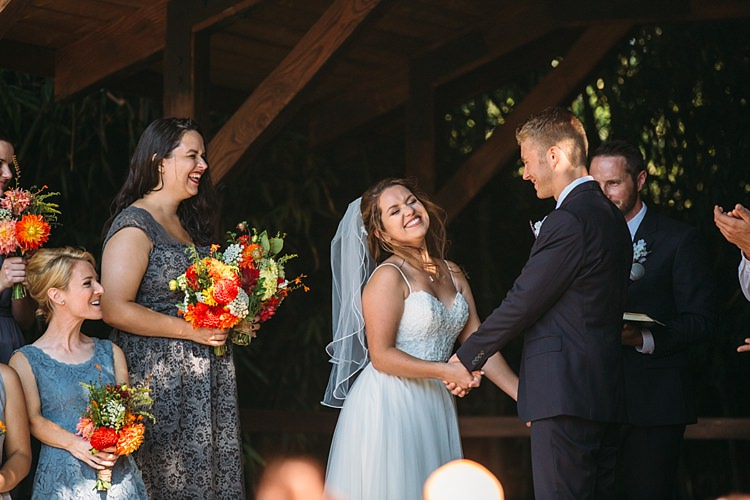 Outdoor Ceremony Bride Lace Tulle Bridal Gown Grey Sash Veil Groom Navy Blue Suit Grey Tie Floral Button Hole Bridesmaids Grey Blue Dresses Bright Orange Red Yellow Bouquets Organic Farm Wedding Washington http://www.katiedayphotos.com/