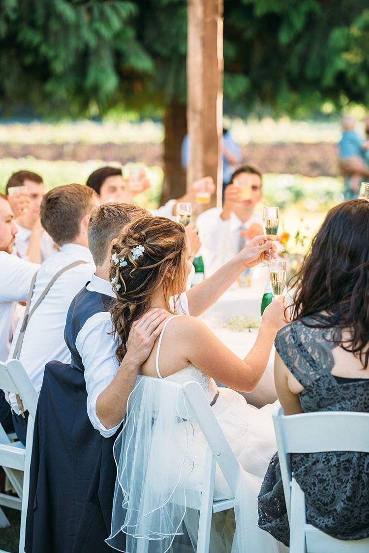 Outdoor Reception Bride Lace Tulle Bridal Gown Grey Sash Loose Curls Hairstyle Flowers Groom Navy Blue Vest White Shirt Guests Cheers Organic Farm Wedding Washington http://www.katiedayphotos.com/