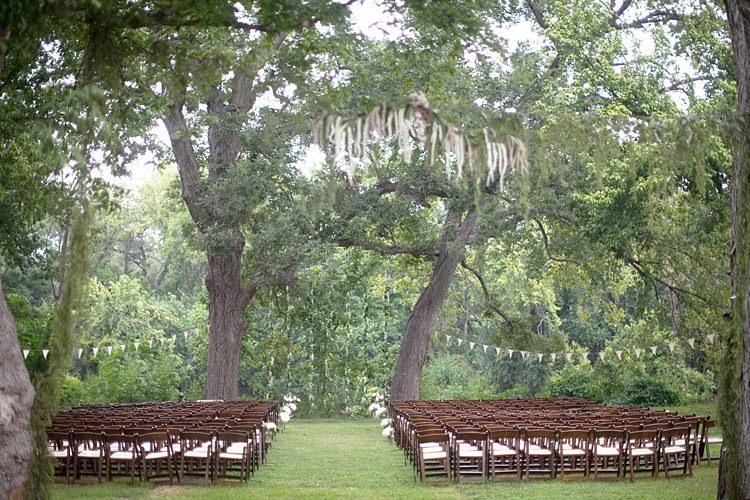 Outdoor Ceremony Hanging Bunting Dark Wooden Chairs Trees Grass Gold & Peach Riverside Garden Wedding http://kellyhornberger.com/