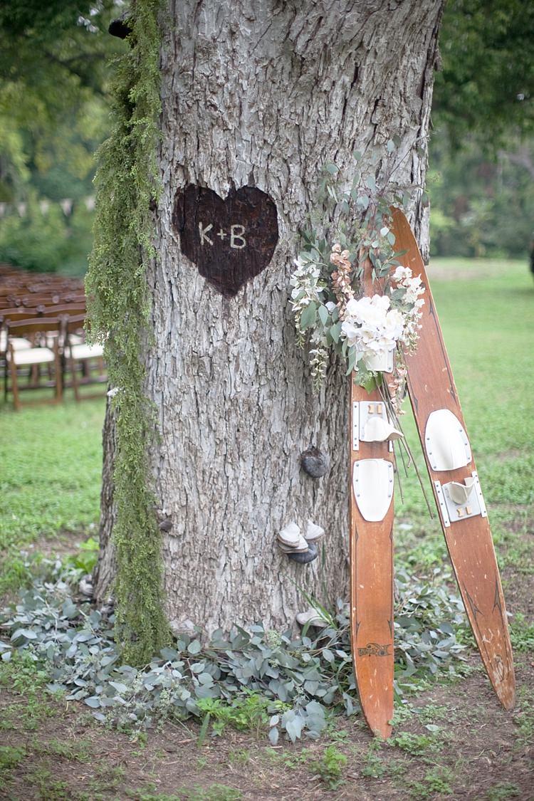 Outdoor Ceremony Tree Carving Heart Initials Wooden Skis Fresh Peach Cream Florals Gold & Peach Riverside Garden Wedding http://kellyhornberger.com/