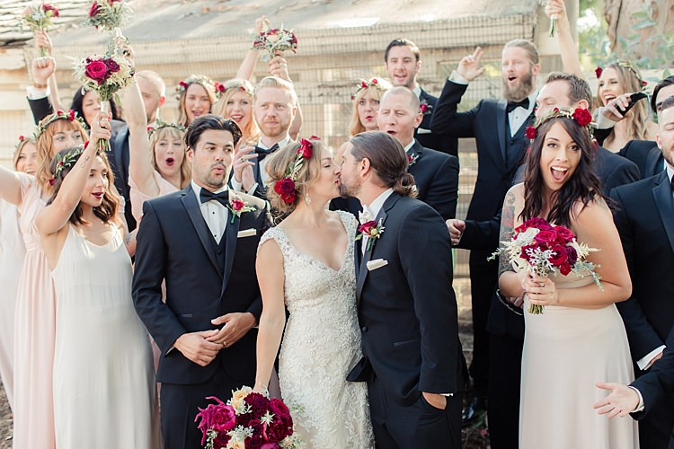 Bridal Party Bride Lace V Neck Bridal Gown Red Maroon Rose Floral Crown Bouquet Groom Black Suit White Shirt Bowtie Rose Buttonhole Bridesmaids Cream Dresses Floral Crowns Groomsmen Black Suits Black Bowties Luxe Outdoor Garden Wedding in California http://figlewiczphotography.com/