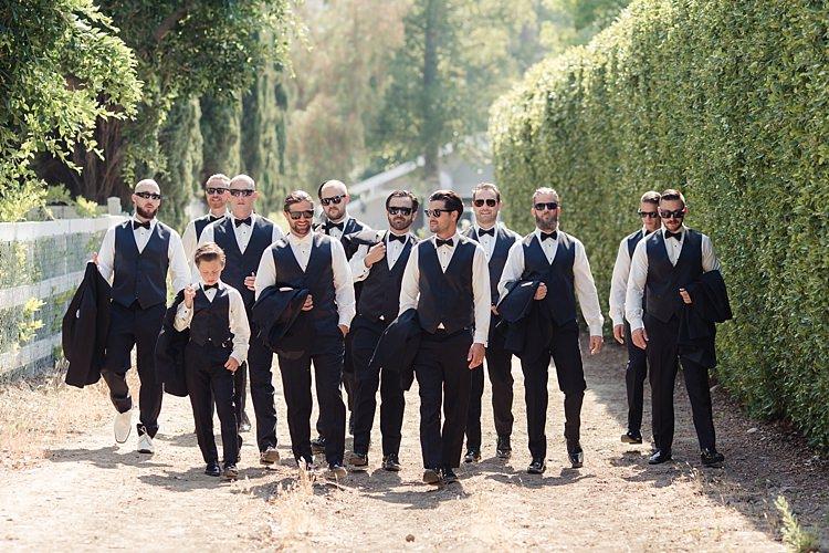 Groom Black Suit Vest White Bowtie Sunglasses Groomsmen Black Suits Black Bowties Page Boy Tall Hedge Trees Luxe Outdoor Garden Wedding in California http://figlewiczphotography.com/