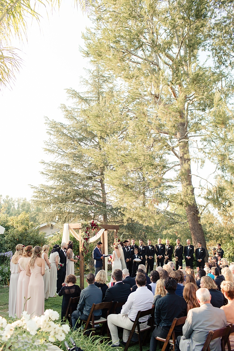 Outdoor Ceremony Bride Lace V Neck Bridal Gown Groom Bridesmaids Groomsmen Guests Wooden Decorated Arch Red Maroon Cream Roses Tall Trees Luxe Outdoor Garden Wedding in California http://figlewiczphotography.com/
