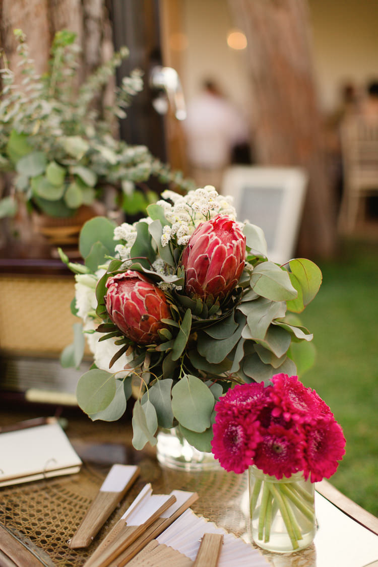 Reception Fresh Multicoloured Florals Red Proteas Glass Vases Paper Fans Homely Vintage Villa Wedding Portugal http://www.mattandlenaphotography.com/