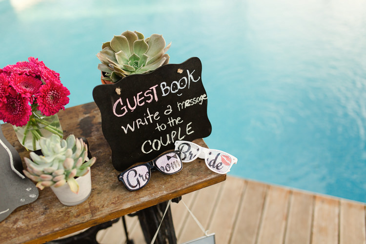 Reception Wooden Guestbook Table Potted Succulents Fresh Pink Florals Glass Vase Fun Bride Groom Sunglasses Chalkboard Sign Pool Homely Vintage Villa Wedding Portugal http://www.mattandlenaphotography.com/