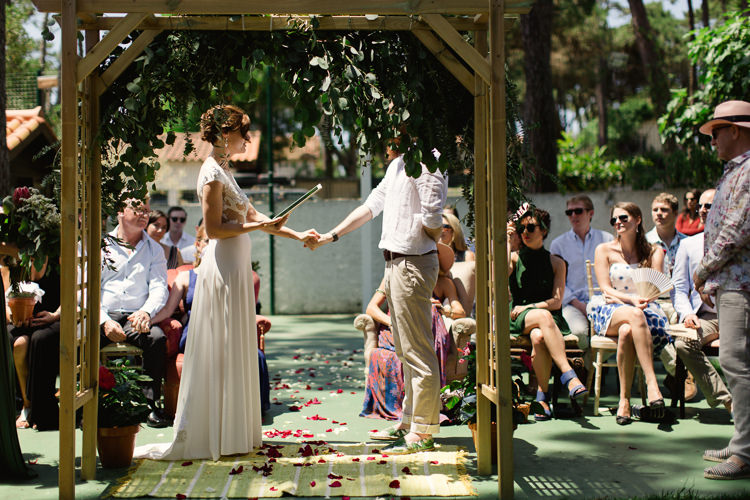 Outdoor Ceremony Bride Lace Illusion Back Bridal Gown Vows Groom Khaki Pants White Shirt Palm Tree Shoes Greenery Archway Guests Homely Vintage Villa Wedding Portugal http://www.mattandlenaphotography.com/