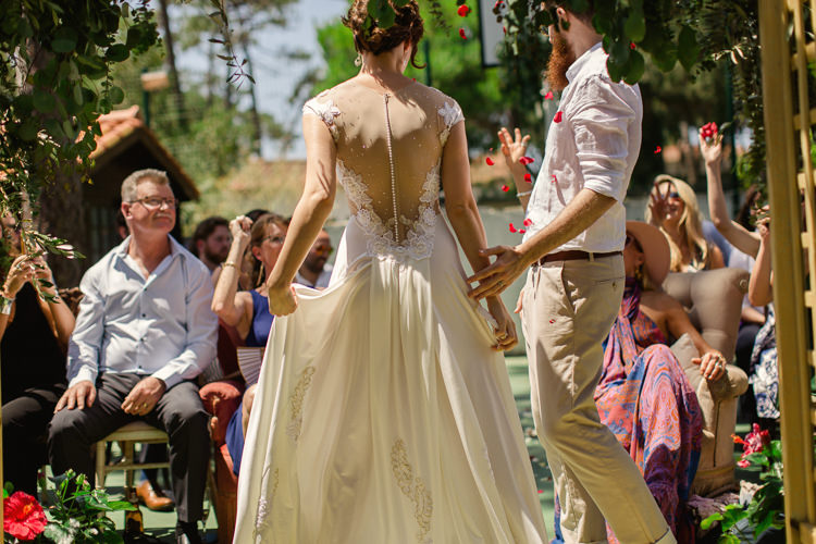 Outdoor Ceremony Bride Lace Illusion Back Bridal Gown Groom Khaki Pants White Shirt Guests Petal Toss Homely Vintage Villa Wedding Portugal http://www.mattandlenaphotography.com/