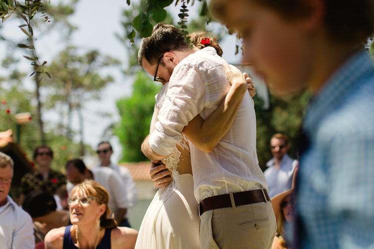 Outdoor Ceremony Bride Lace Illusion Back Bridal Gown Groom Khaki Pants White Shirt Hug Guests Homely Vintage Villa Wedding Portugal http://www.mattandlenaphotography.com/