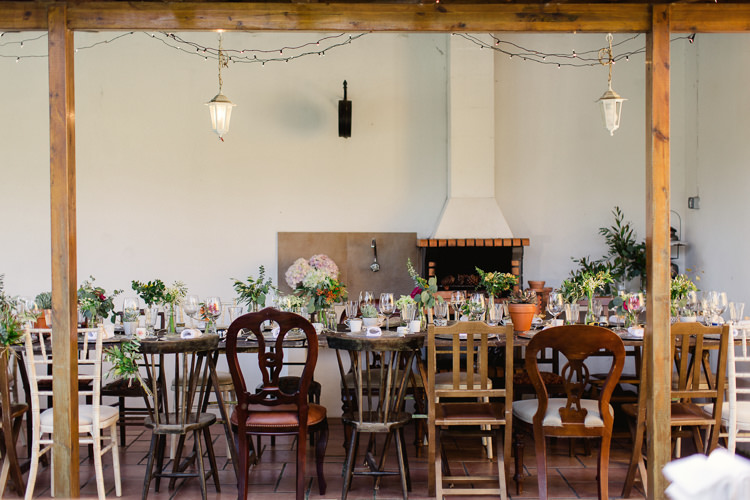 Reception Wooden Table Assorted Wooden Chairs Fresh Florals Glass Vases Potted Succulents Brick Fireplace Hanging Fairy Lights Lanterns Homely Vintage Villa Wedding Portugal http://www.mattandlenaphotography.com/