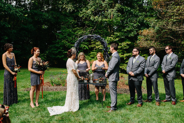 Outdoor Ceremony Floral Archway Bride Strapless Lace Watters Bridal Gown Sheer Top Birdcage Veil Groom Grey Suit Green Bowtie Sisters Officiants Bridesmaids Groomsmen Art Nouveau Autumn Burgundy Wedding http://www.jbonadiophoto.com/