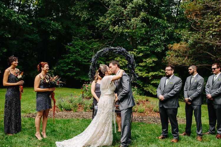 Outdoor Ceremony Floral Archway Bride Strapless Lace Watters Bridal Gown Sheer Top Birdcage Veil Groom Grey Suit Green Bowtie Kiss Bridesmaids Groomsmen Art Nouveau Autumn Burgundy Wedding http://www.jbonadiophoto.com/