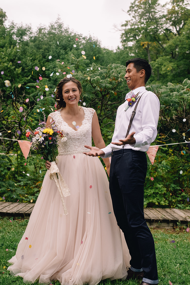 Bright Confetti Bride Allure Champagne Lace Tulle Bridal Gown Multicoloured Floral Bouquet Lace Ribbon Groom White Shirt Brown Leather Suspenders Navy Pants Multicoloured Floral Buttonhole Bunting Woodland Waterfall Mint Wedding Ontario http://www.laurenmccormickphotography.com/
