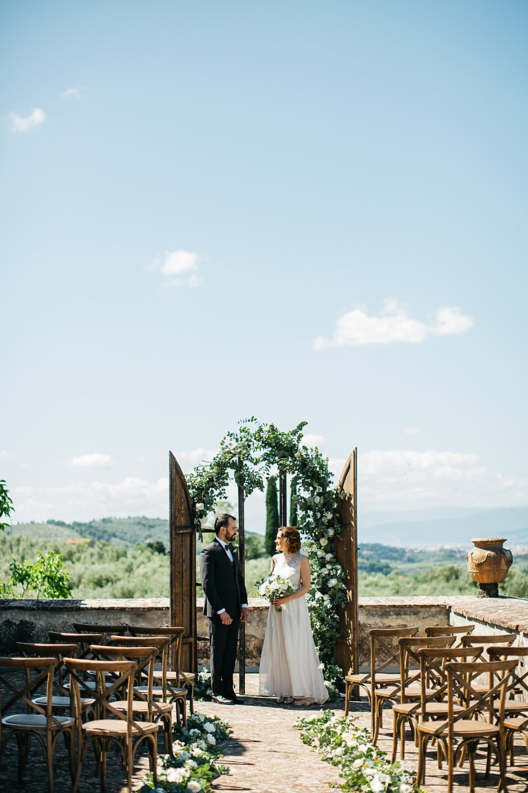Outdoor Ceremony Bride High Neck Lace Tulle Bridal Gown Buttons Bouquet Groom Charcoal Pinstripe Suit Green Patterned Bowtie Wooden Archway White Roses Greenery Wooden Chairs Rustic Chic Greenery Wedding Ideas in Tuscany http://www.tastino0.it/