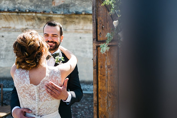Outdoor Ceremony Bride High Neck Lace Tulle Bridal Gown Buttons Groom Charcoal Pinstripe Suit Green Patterned Bowtie Wooden Archway Rustic Chic Greenery Wedding Ideas in Tuscany http://www.tastino0.it/