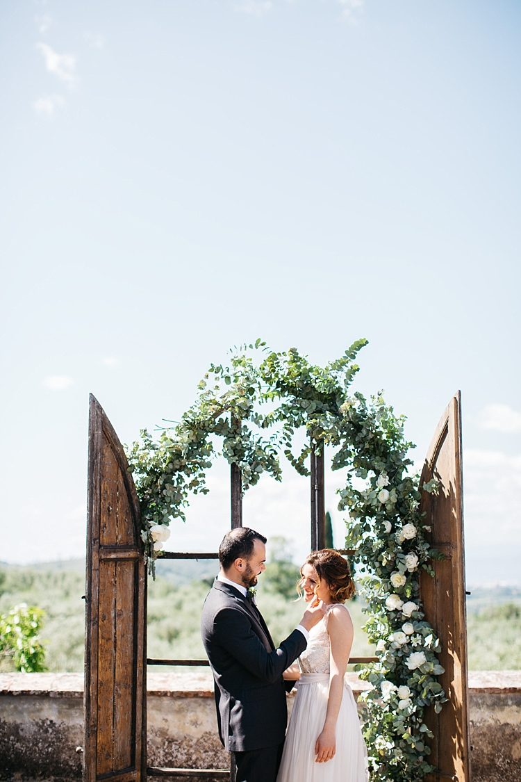 Outdoor Ceremony Bride High Neck Lace Tulle Bridal Gown Buttons Groom Charcoal Pinstripe Suit Green Patterned Bowtie Wooden Archway White Roses Greenery Rustic Chic Greenery Wedding Ideas in Tuscany http://www.tastino0.it/