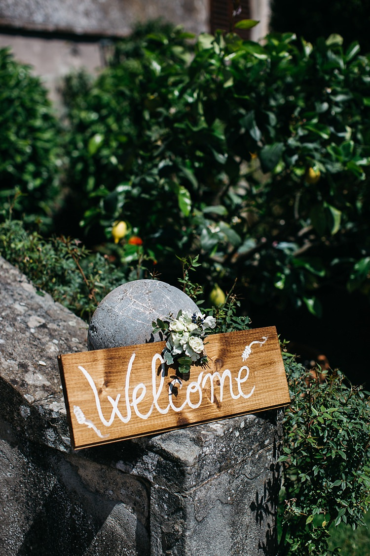 Outdoor Ceremony Wooden Welcome Sign White Handwriting Floral Decoration Stone Fence Trees Rustic Chic Greenery Wedding Ideas in Tuscany http://www.tastino0.it/