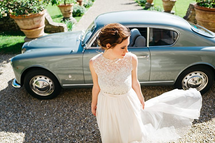 Bride High Neck Lace Tulle Bridal Gown Loose Curls Hairstyle Vintage Grey Car Large Potted Plants Rustic Chic Greenery Wedding Ideas in Tuscany http://www.tastino0.it/