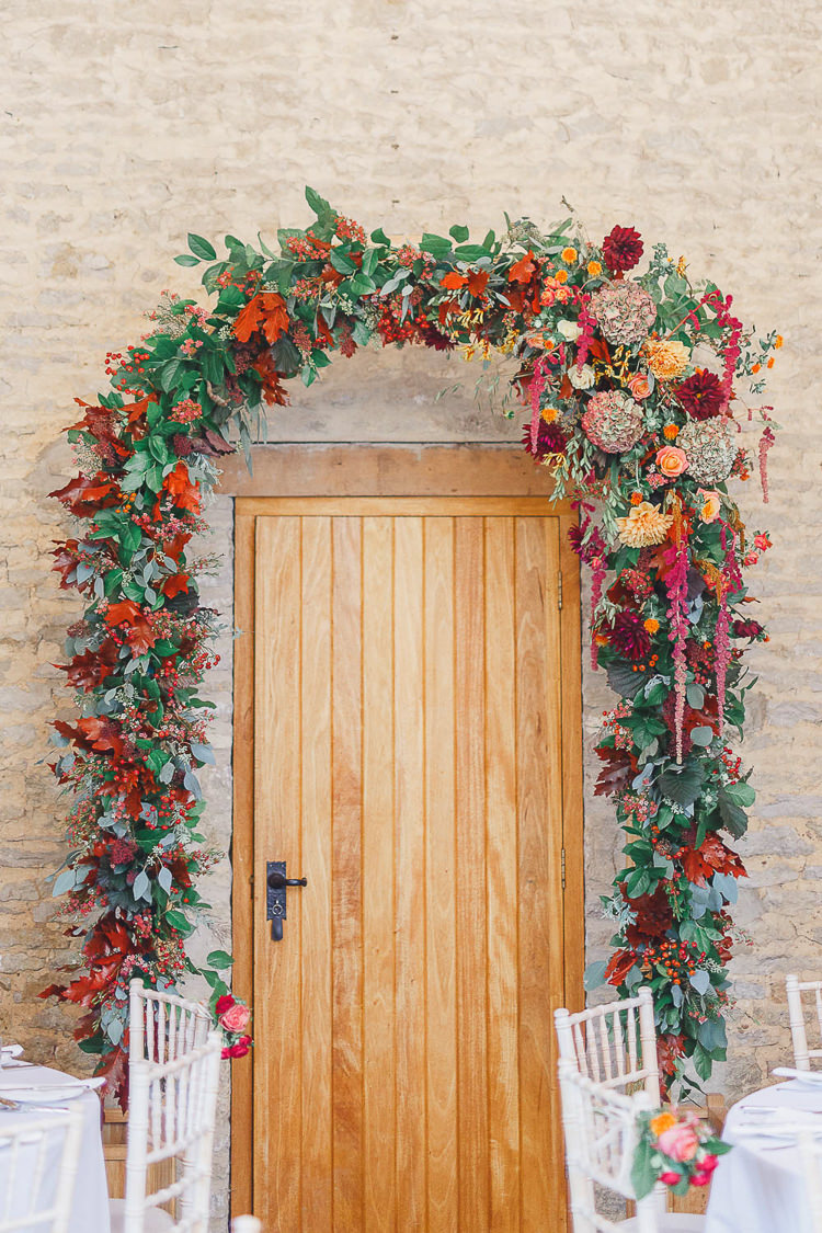 Arch Flowers Red Orange Dahlia Rose Arrangement Foliage Doorway Berry Magical Fairy Lit Autumn Barn Wedding http://whitestagweddings.com/