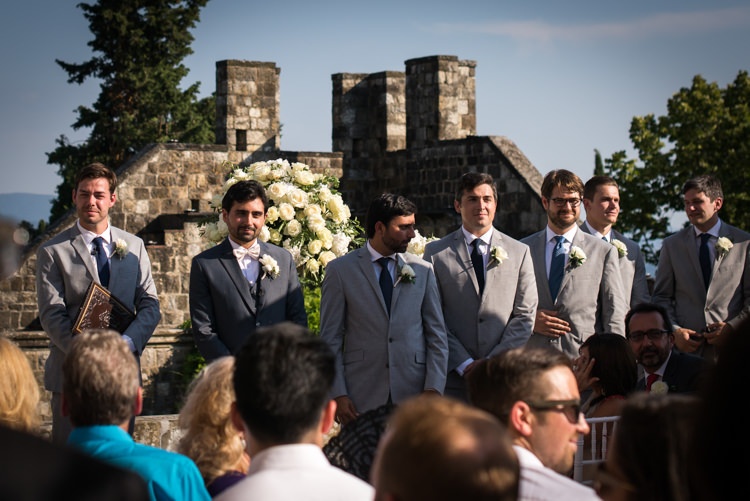 Outdoor Ceremony Groom Black Suit White Bowtie Floral Buttonhole Groomsmen Celebrant Guests White Roses Romantic Outdoor Castle Tuscany Wedding http://www.natalymontanari.com/
