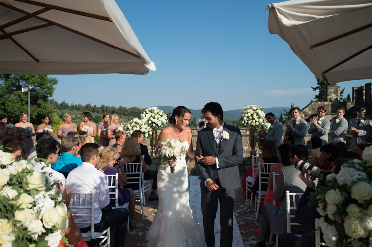 Outdoor Ceremony Bride Fitted Lace Mermaid Bridal Gown Groom Black Suit White Shirt White Bowtie Guests White Chairs White Roses Umbrellas Romantic Outdoor Castle Tuscany Wedding http://www.natalymontanari.com/
