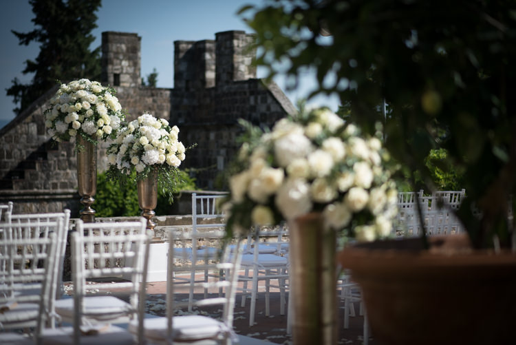 Outdoor Ceremony Metallic Pillars White Roses White Chairs Potted Plants Romantic Outdoor Castle Tuscany Wedding http://www.natalymontanari.com/