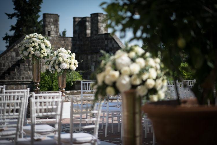 Outdoor Ceremony Metallic Pillars White Roses White Chairs Potted Plants Romantic Outdoor Castle Tuscany Wedding http://www.natalymontanari.com/