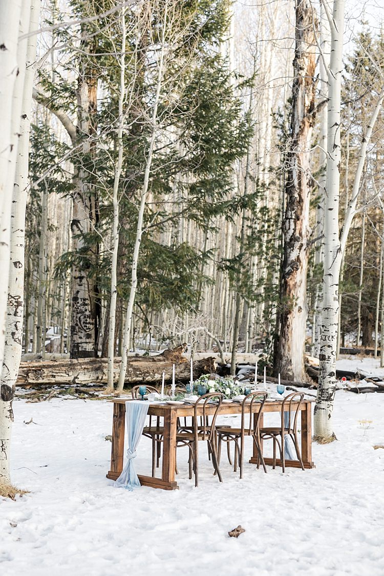 Outdoor Reception Wooden Table Blue Fabric Candlesticks Fresh Florals Tall Trees Snowy Winter Wonderland Anniversary Shoot http://ryannlindseyphotography.com/
